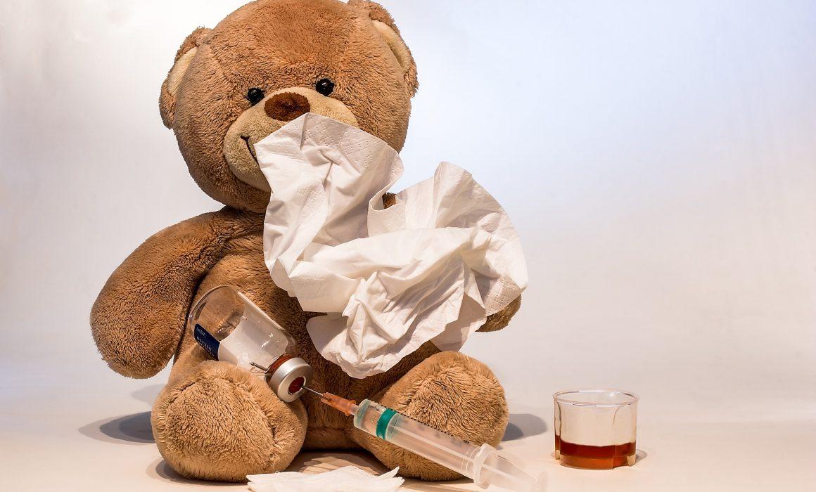 Teddybär mit Taschentuch vor der Schnute und Medizin vor sich.